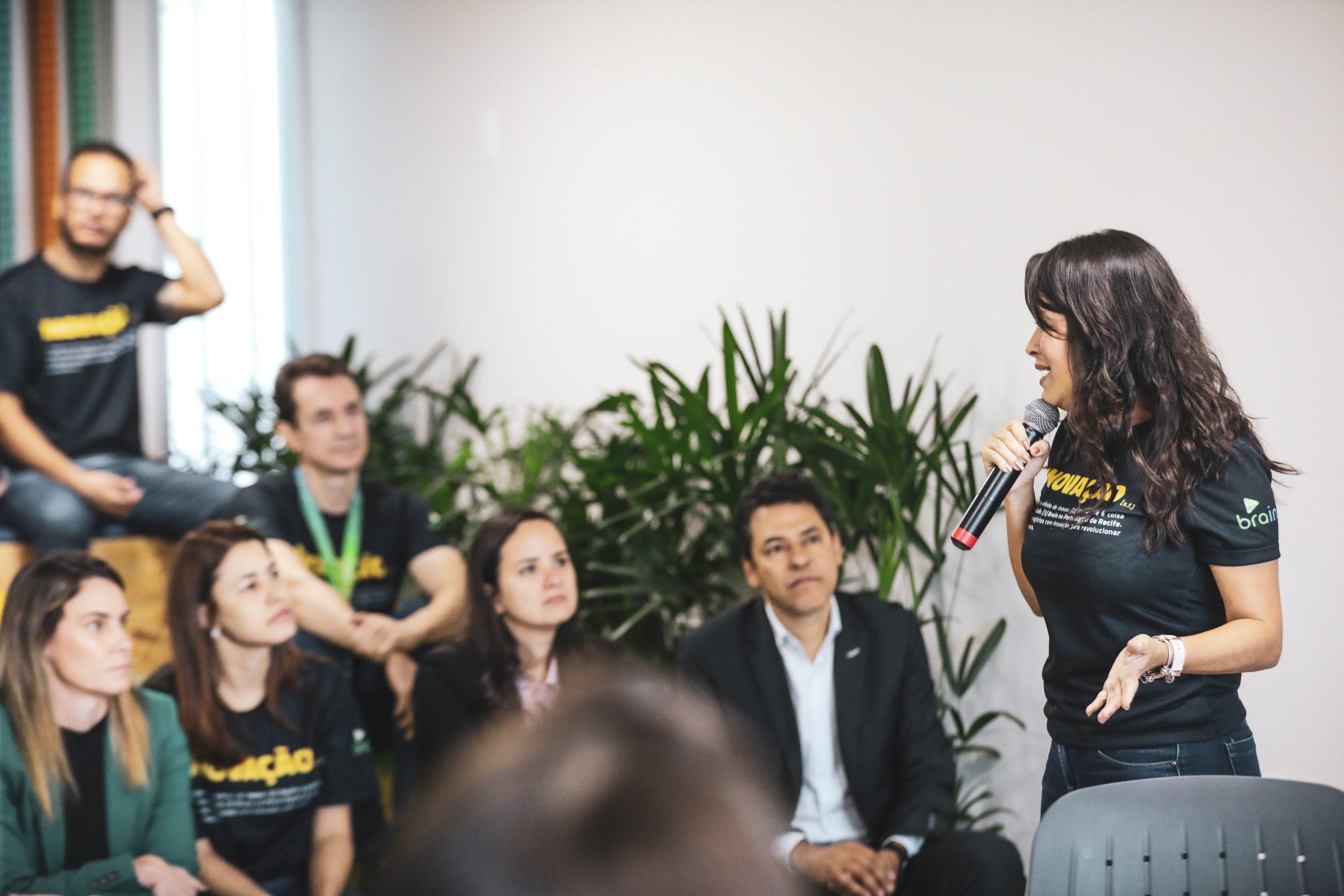 Foto da Zaima, Presidente do Brain, durante uma palestra.