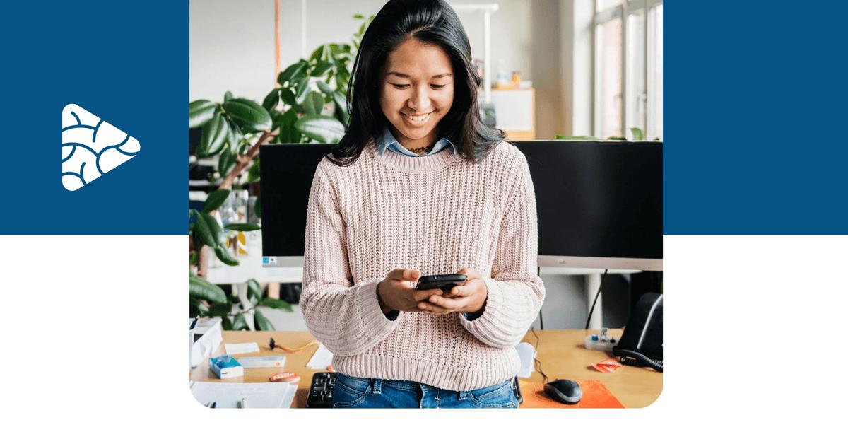 Foto de uma mulher usando o celular no ambiente de trabalho, representando a gamificação nas empresas.