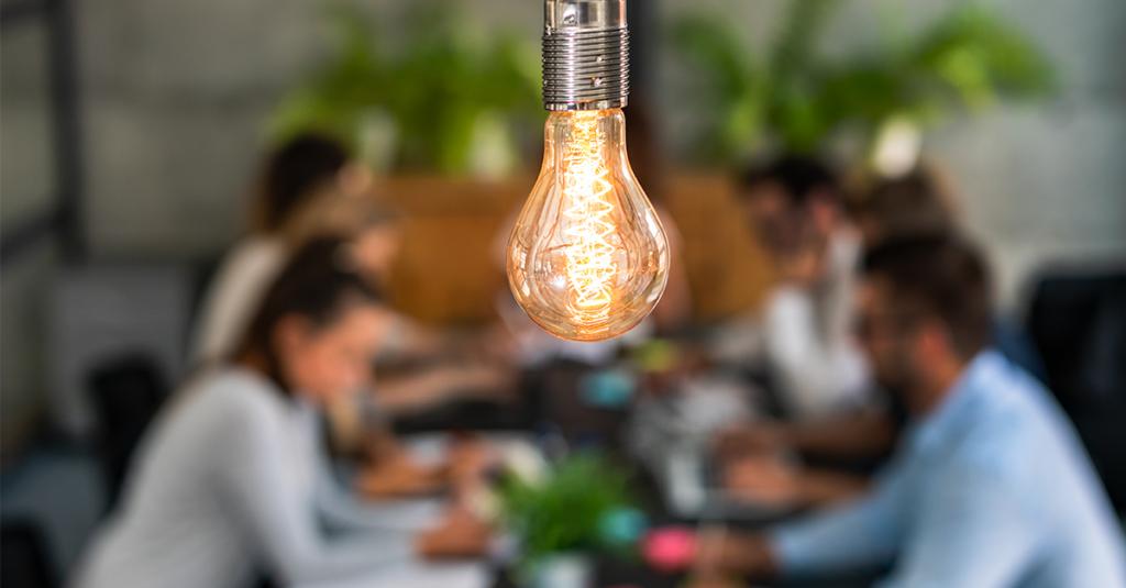 Foto de uma lâmpada com pessoas ao fundo.